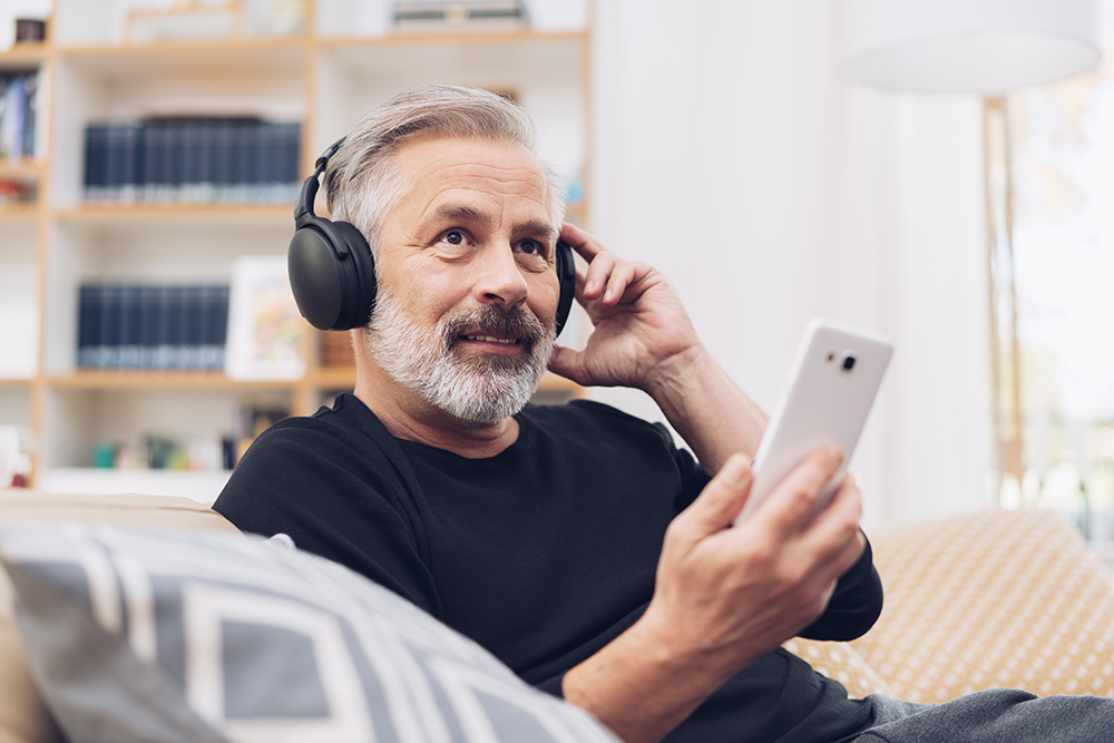 Portrait of a middle-aged man using his mobile phone for listening to Bob Russo's Realty Speak podcast: 1031 Like Kind Exchanges online through modern headphones at home